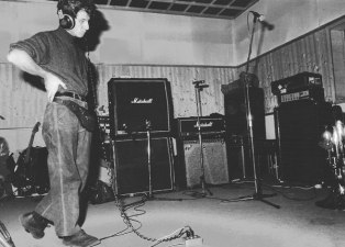"""Dicembre 1990, negli studi Sub Cave alle EX-CASERME ROSSE (BO) gli amici della Banda Osiris accorrono a supportare i nostri, laddove la loro imperizia tecnica li lascia delusi ai bordi delle piste (del mixer). Qui vediamo il prof. Gian Luigi Carlone Jr. che riascolta il suo yodel, gorgheggiato all'interno di """"Tostapanino Valzer""""."""